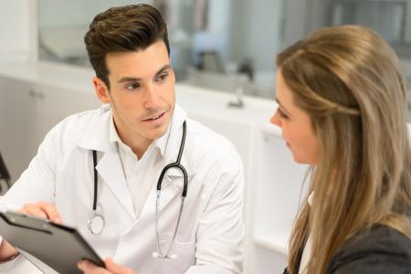 Pacjent: Portret słuchania lekarza do pacjenta wyjaśniając jej bolesne w jego biurze Zdjęcie Seryjne