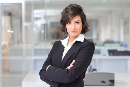 business woman standing: Portrait of a business woman in an office. Crossed arms