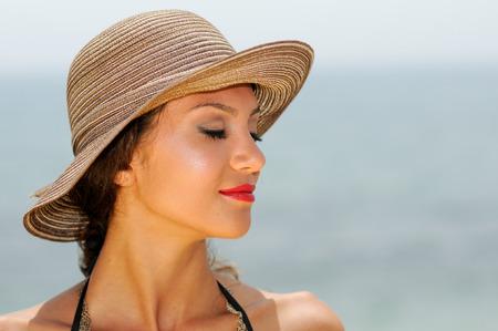 perfil de mujer rostro: Close up retrato de una mujer hermosa que lleva sombrero de sol en una playa tropical con los ojos cerrados