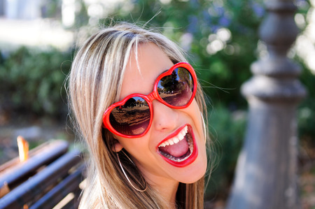 Funny girl with red heart glasses in a park Banco de Imagens