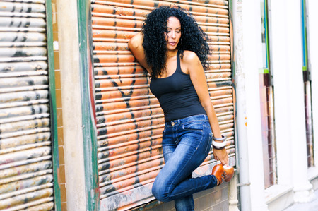 Portrait of a young black woman, model of fashion wearing high heels, in urban background Stock Photo