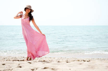 Portrait of a beautiful woman with long pink dress and sun hat on a tropical beach  photo