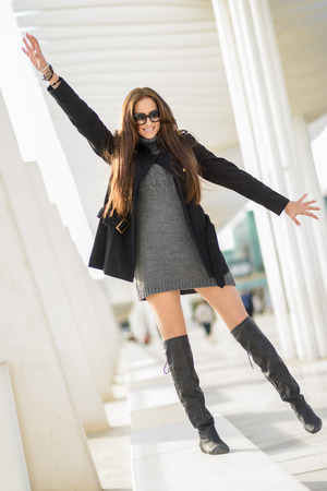 walking boots: Portrait of a funny young woman, wearing casual clothes, with long hair in urban background  Stock Photo