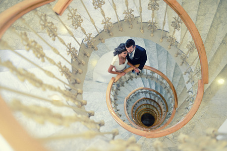 Just married couple together in a spiral staircase photo