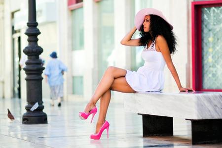 도시 배경에 아프리카 헤어 스타일 패션 드레스를 입고 및 태양 모자의 젊은 흑인 여성 모델의 초상화