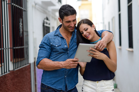 citylife: Portrait of beautiful couple with tablet computer in urban background Stock Photo