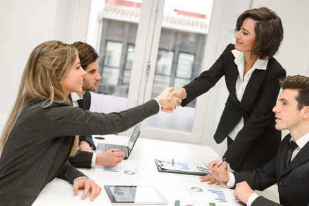 Four business people shaking hands, finishing up a meeting  photo