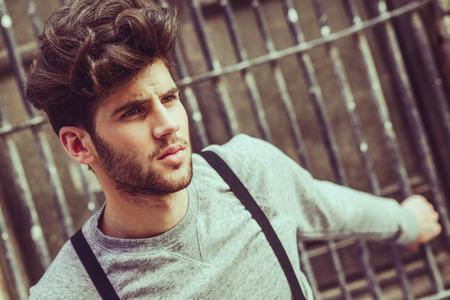 coiffer: Portrait de jeune homme portant des bretelles en arrière-plan urbain Banque d'images