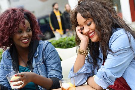 socializando: Retrato de dos mujeres que toman una copa en un bar.