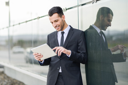 Portrait of attractive young businessman smiling with a tablet computer in an office building photo