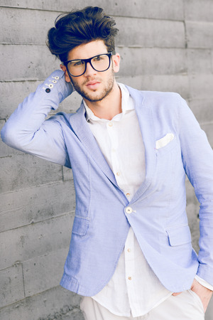 blazer: Portrait of cheerful trendy guy with black eyeglasses on wearing blue blazer jacket
