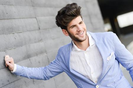 blazer: Portrait of a young handsome man, model of fashion, smiling in urban background wearing blue blazer jacket