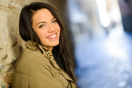 Portrait of brunette young woman with green eyes, wearing a coat, in urban background photo