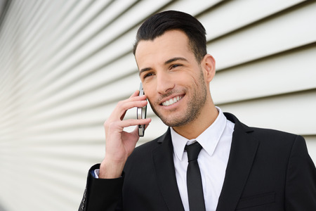 Portrait of an attractive young businessman smiling on the phone in an office building photo