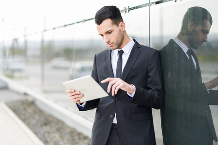 Portrait of attractive young businessman with a tablet computer in an office building photo