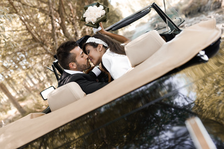 Just married couple together in an old car Foto de archivo