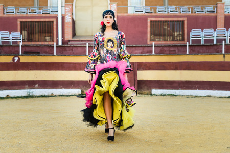 spanish style: Portrait of a pretty woman, model of fashion, wearing a dress in a bullring. Spanish style