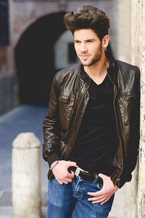 Portrait of a young handsome man, model of fashion, with modern hairstyle in urban background wearing blue jeans and leather jacket photo