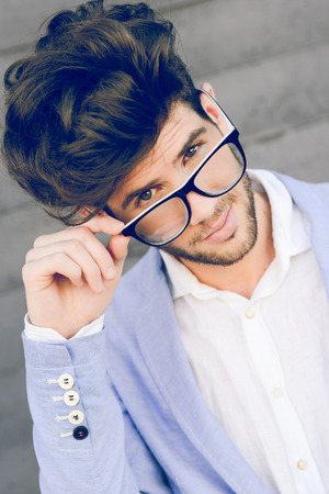 Portrait of cheerful trendy guy with black eyeglasses on wearing blue blazer jacket photo