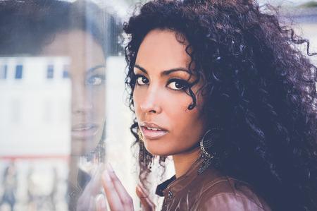 брюнетка: Портрет молодой чернокожей женщиной, афро прически, в городской фон Фото со стока