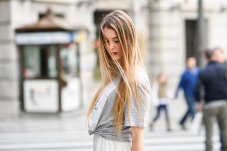 cabello rubio: Retrato de la muchacha rubia joven con ropa casual en el fondo urbano