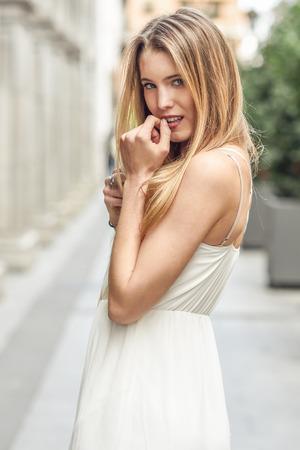 Portrait of beautiful blonde girl in urban background wearing white dress