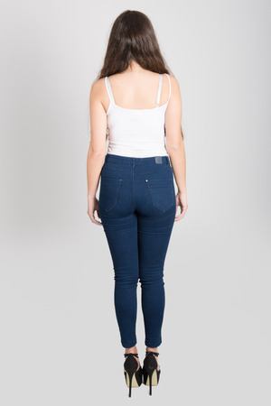 hair back: Back view of young woman with long hair wearing white t-shirt and blue jeans on white background