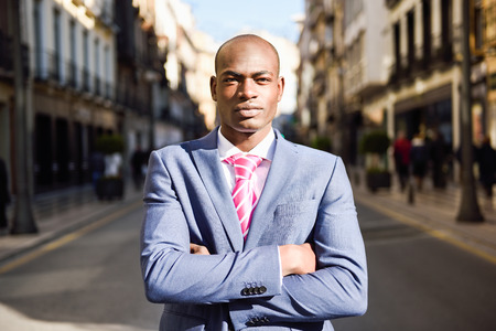 Portrait of handsome black man wearing suit in urban background photo