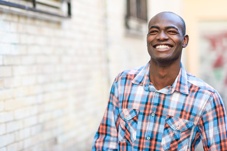 Portrait of black man very happy, smiling in urban background photo