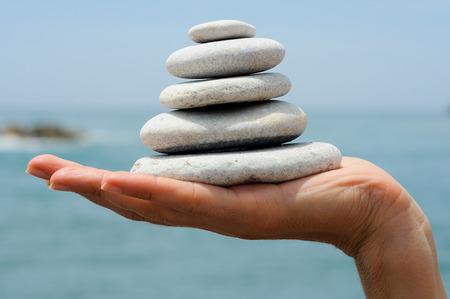 海の背景を持つ女性の手で杭の砂利のクローズ アップ 写真素材