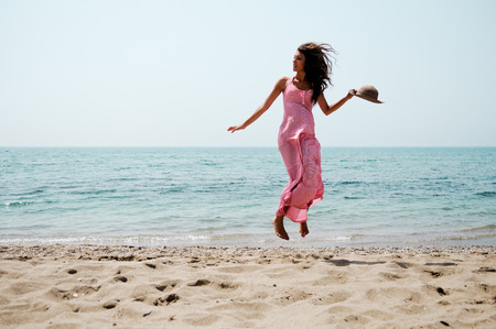 Portrait of a beautiful woman with long pink dress jumping on a tropical beach photo