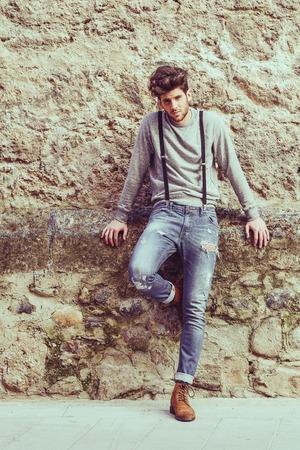 modelos hombres: Retrato de joven hombre que llevaba tirantes y los pantalones vaqueros azules en fondo urbano con corte de pelo moderno Foto de archivo