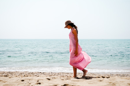 Portrait of a beautiful woman with long pink dress and sun hat on a tropical beach Standard-Bild