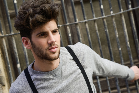 urban style: Portrait of young man wearing suspenders in urban background