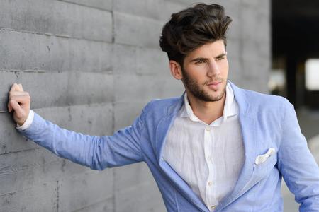 estilo urbano: Retrato de un hombre joven y guapo, modelo de moda, con el peinado moderno en el medio urbano
