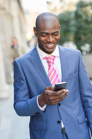 smiling businessman: Portrait of a black businessman wearing suit reading his smart phone in urban background