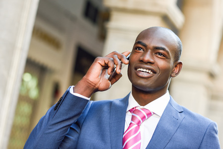 Portrait of a black businessman wearing suit talking with his smartphone in urban background