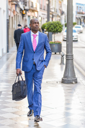 portrait man: Portrait of a black business man walking on the street with a modern briefcase