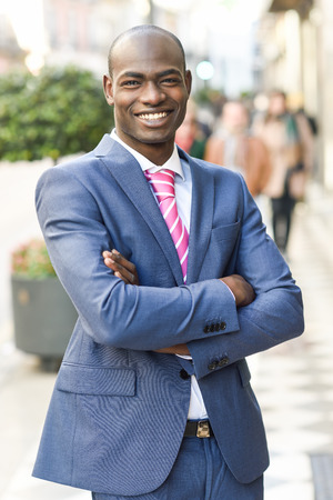 Portrait of handsome black man wearing suit and smiling in urban background