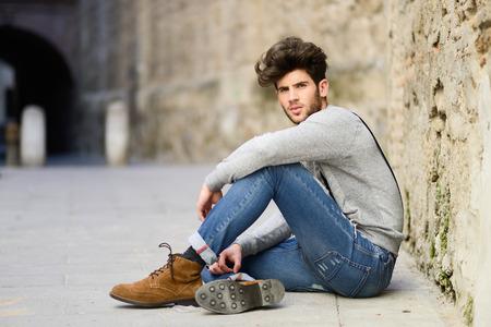 Portret van jonge man het dragen van bretels zittend op de vloer in de stedelijke achtergrond
