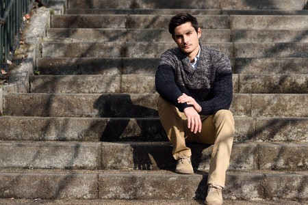 Portrait of a young handsome man, model of fashion, with modern hairstyle sitting on stairs, wearing casual clothes. photo