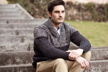 sueteres: Retrato de un hombre hermoso joven, modelo de moda, con el peinado moderno sentado en las escaleras, con ropa casual.