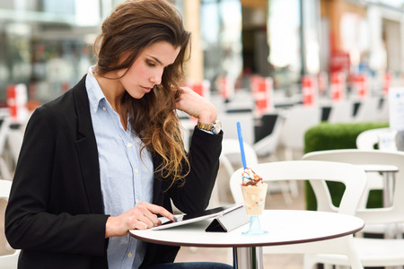 Portrait of a woman looking at her tablet computer, sitting in a coffee shop photo
