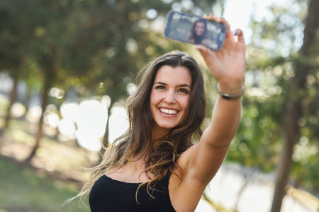 Portrait of a beautiful young woman selfie in the park with a smartphone Banque d'images