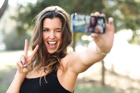 Portrait of a beautiful young woman selfie in the park with a smartphone doing v sign Foto de archivo