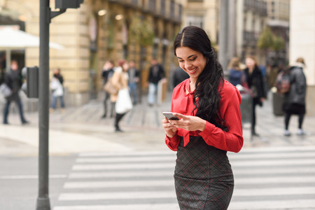 latin girls: Portrait of hispanic bussinesswoman in urban background looking at her mobile phone