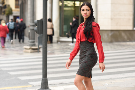 formal clothes: Portrait of hispanic businesswoman in urban wearing red shirt and skirt Stock Photo