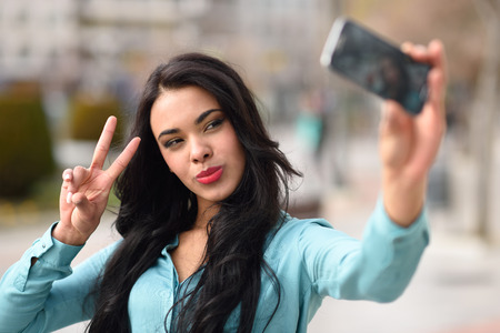 latin girls: Portrait of a beautiful young woman, using braces, selfie in the street with a smartphone doing v sign Stock Photo