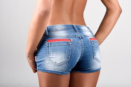 culo: Donna che indossa shorts in denim con una bella vita. Studio shot