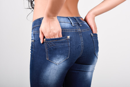 Woman wearing blue jeans with a beautiful waist. Studio shot Stock Photo